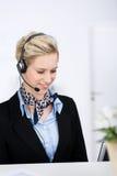 Kvinnlig kundtjänstledare med hörlurar med mikrofon Royaltyfri Bild