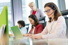 Kvinnlig kundtjänstrepresentant som använder bärbara datorn medan kollegor i bakgrund på kontoret arkivfoto