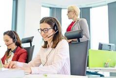 Kvinnlig kundtjänstrepresentant som använder hörlurar med mikrofon medan kollegor i bakgrund på kontoret royaltyfria bilder