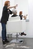 Kvinnlig kvinna för frisörGiving Haircut To pensionär Royaltyfri Foto