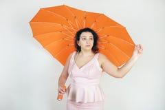 Kvinnlig kvinna med plus formatkroppen i rosa klänning med det orange stor hjärta formade paraplyet som poserar på vit bakgrun arkivfoton