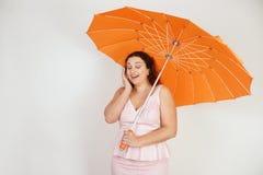 Kvinnlig kvinna med plus formatkroppen i rosa klänning med det orange stor hjärta formade paraplyet som poserar på vit bakgrun arkivfoto