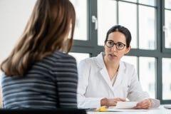 Kvinnlig läkare som lyssnar till hennes patient under konsultation royaltyfria foton