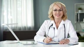 Kvinnlig läkare som sitter på tabellen och att le in camera, arbetande sjukdomshistorier arkivfoto