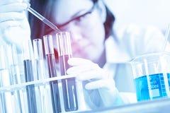 Kvinnlig läkarundersökning eller vetenskaplig forskare som använder provröret på arbete Royaltyfria Bilder