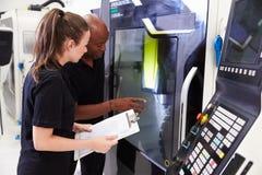 Kvinnlig lärling som arbetar med maskineri för teknikerOn CNC Royaltyfri Fotografi