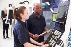 Kvinnlig lärling som arbetar med maskineri för teknikerOn CNC Royaltyfri Foto