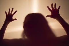 Kvinnlig läskig kontur bak en tygvägg Royaltyfri Bild