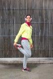 Kvinnlig löpare för kondition som sträcker benet Arkivbilder