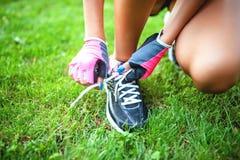 Kvinnlig löpare och idrottsman nen som förbereder skor för att jogga Royaltyfri Fotografi