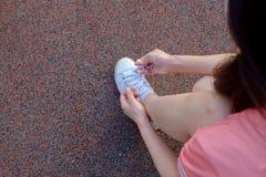 Kvinnlig löpare som binder hennes sportsko Arkivbild