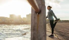 Kvinnlig löpare som sträcker vid sjösidapromenad Royaltyfri Foto