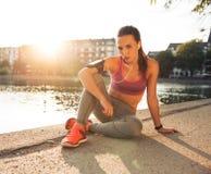 Kvinnlig löpare som tar en vila från utbildning Arkivbilder