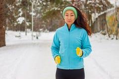 Kvinnlig löpareslingaspring i kallt snöa väder Asiatisk kinesisk idrottsman nenkvinnautbildning för maraton som joggar utanför i  arkivfoto