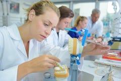 Kvinnlig labbtekniker som arbetar på tandproteser arkivfoto