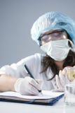 Kvinnlig laborant i ansikts- maskering och skyddande handskar som gör anmärkningar om aktuellt experiment royaltyfri fotografi