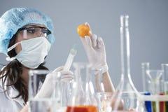 Kvinnlig laborant i ansikts- maskering och skyddande handskar som gör anmärkningar om aktuellt experiment royaltyfri bild