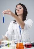 Kvinnlig laboratoriumpersonal som arbetar med flaskor som fylls med flytande Royaltyfri Foto