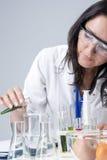 Kvinnlig laboratoriumpersonal som arbetar med flaskor som fylls med flytande Arkivbilder