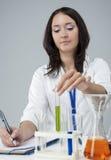 Kvinnlig laboratoriumpersonal som arbetar med flaskor som fylls med flytande Arkivbild