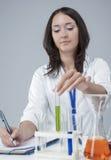 Kvinnlig laboratoriumpersonal som arbetar med flaskor som fylls med flytande Arkivfoto
