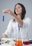 Kvinnlig laboratoriumpersonal som arbetar med flaskor som fylls med flytande i labb Arkivbild