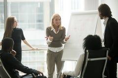 Kvinnlig lagledare eller affärslagledare som ger presentation till empl royaltyfria foton