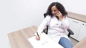 Kvinnlig latinsk kvinnlig doktor som sitter för att koppla av i hennes konsulterande rum med stetoskopet på hennes hals som talar royaltyfri fotografi