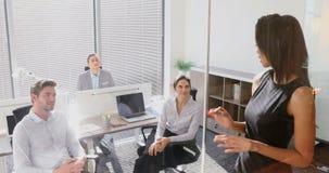 Kvinnlig ledare med hans kollegor som diskuterar över det glass brädet 4k arkivfilmer