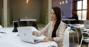 Kvinnlig ledare som använder bärbara datorn 4k lager videofilmer