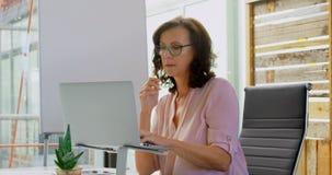 Kvinnlig ledare som använder bärbara datorn på skrivbordet 4k arkivfilmer
