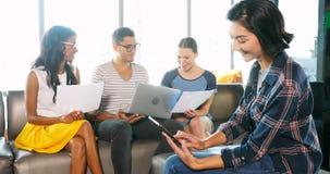 Kvinnlig ledare som använder den digitala minnestavlan medan kollegor som arbetar på bärbara datorn 4k stock video