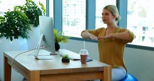 Kvinnlig ledare som gör övning på övningsboll på hennes skrivbord lager videofilmer