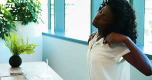 Kvinnlig ledare som gör sträcka övning, medan arbeta på hennes skrivbord lager videofilmer