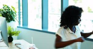 Kvinnlig ledare som gör sträcka övning, medan arbeta på hennes skrivbord stock video
