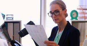 Kvinnlig ledare som granskar det fångade fotografiet på hennes skrivbord 4k stock video