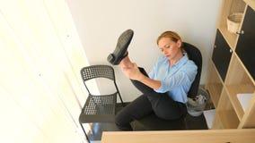 Kvinnlig ledare som utför sträckning på hennes arbetsplats i regeringsställning 4k ultrarapid lager videofilmer