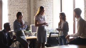 Kvinnlig ledareledare som rymmer det pappers- rapportsamtalet som instruerar lagarbetare arkivfilmer