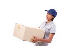 Kvinnlig leveranspersonal som bär den tunga jordlottlådaasken Royaltyfri Bild