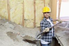 Kvinnlig leverantör som gräver sand på konstruktionsplatsen arkivbilder
