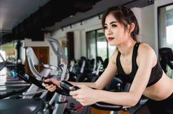 Kvinnlig livsstil genom att använda utrustningmotionscykelen för utbildning av cardio genomkörare royaltyfria foton