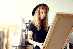 Kvinnlig lockig konstnär With Canvas arkivbild