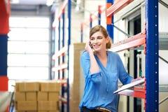 Kvinnlig logistikarbetare som kontrollerar materielet och talar på mobiltelefonen i lager Royaltyfri Bild