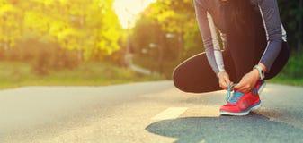 Kvinnlig löpare som binder henne skor som förbereder sig för en jogga Fotografering för Bildbyråer