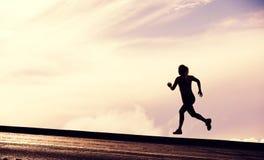 Kvinnlig löparekontur, kvinnaspring in i solnedgång Fotografering för Bildbyråer