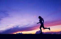 Kvinnlig löparekontur, kvinnaspring in i solnedgång Arkivbild