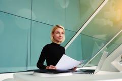 Kvinnlig lyckad ekonom som drömmer om något, medan sitta med bärbar datordatoren i modernt kontor arkivbilder