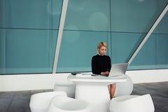 Kvinnlig lyckad entreprenör som söker på nödvändig information om bärbar datordator för hennes nya projekt arkivfoto