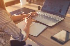Kvinnlig märkes- användande bärbar dator som skissar på den tomma notepaden Kvinnahandhandstil i anteckningsbok på träskrivbordet royaltyfria bilder