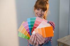Kvinnlig målare som hemma rymmer färgpalletes royaltyfri fotografi
